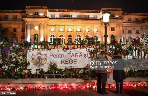People stand in front of flowers and candles displayed on December 13 2017 outside the former Royal Palace that houses the National Arts Museum in...