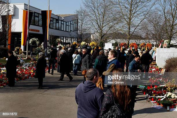 People stand in front of flowers and candles outside Albertville high school on March 21 2009 in Winnenden near Stuttgart Germany 17 year old Tim...