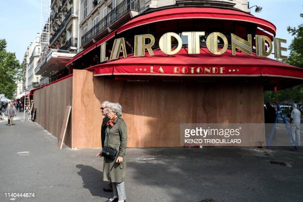 People stand in front of La Rotonde restaurant which is protected with wooden planks in the district of Montparnasse in the French capital prior to...