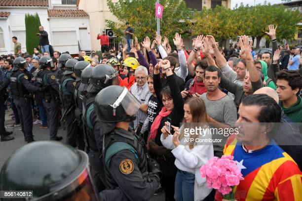 People stand in front of Spanish Guardia Civil officers outside a polling station in San Julia de Ramis on October 1 on the day of a referendum on...