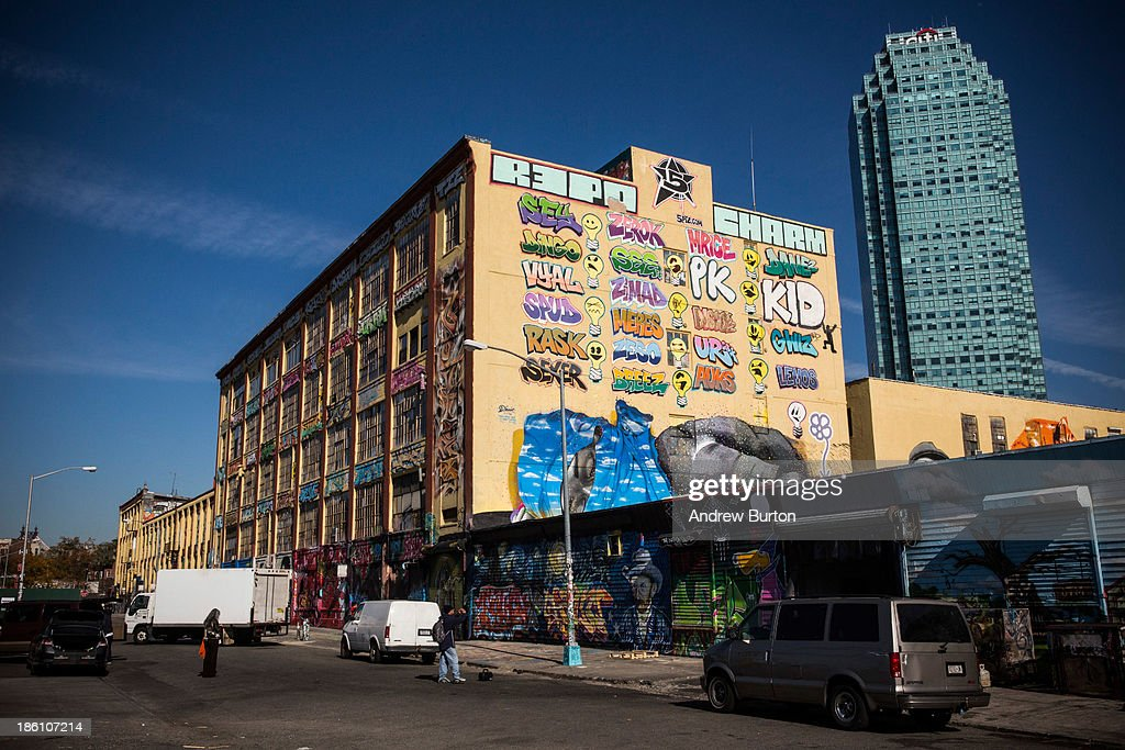 People stand in front of the 5 Pointz Building, a landmark in the New York graffiti scene that has attracted artists from around the globe, on October 28, 2013 in the Long Island City neighborhood of the Queens borough of New York City. The artists that have been using 5 Pointz to paint for the past two decades are currently in a battle with the building's owners, who want to tear the building down to build apartment high rises worth $400 million. The 5 Pointz artistic community have also called on street artist Banksy who is currently in the midst of a high profile 'month in residence' series, creating work through out the streets of New York, to weigh in on the battle, though so far the artist has stayed silent. Meres One says he is prepared to chain himself to the building, should demolition move forward.