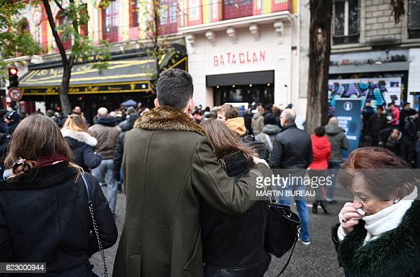 People stand in front of the Bataclan concert hall in Paris, on November 13 during a ceremony marking the first anniversary of the Paris terror...
