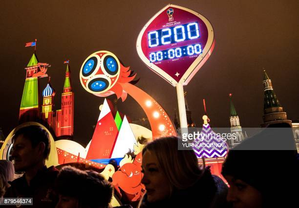 People stand in front of the digital FIFA World Cup 2018 countdown clock which shows exactly 200 days before the beginning of the 2018 World Cup...