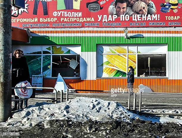 People stand in front of the facade of a local shop which was damaged by a shockwave from a meteor in the Urals city of Chelyabinsk on February 15...