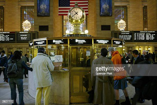 People stand in front of the famous clock at Grand Central Station October 22, 2003 in New York City. Grand Central Station, which opened in 1913, is...