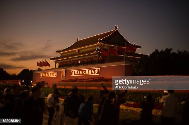 People stand in front of the Forbidden City in Beijing on September 28, 2017. China will convene its 19th Party Congress on October 18, state media...
