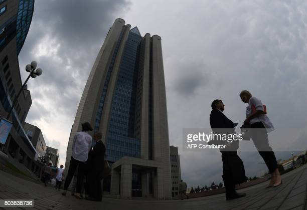 People stand in front of the headquarters of Gazprom during the the annual general meeting of the company's shareholders in Moscow on June 30 2017 /...