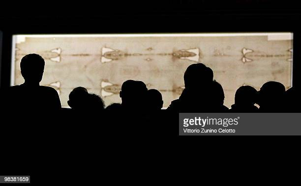 People stand in front of the Holy Shroud during the Solemn Exposition Of The Holy Shroud on April 10 2010 in Turin Italy The Holy Shroud will be...
