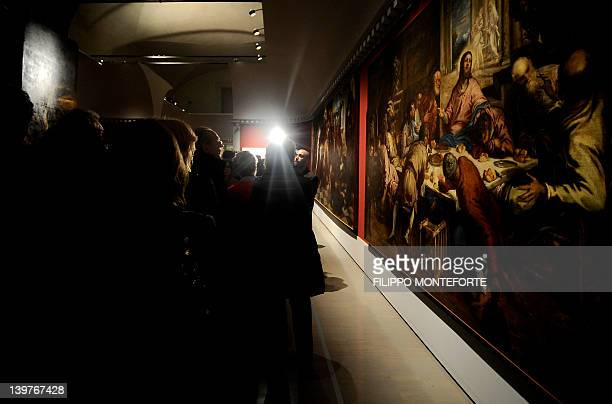 People stand in front of The last supper by Italian painter Jacopo Robusti known as Tintoretto in Rome's Scuderie del Quirinale on February 24 2012...