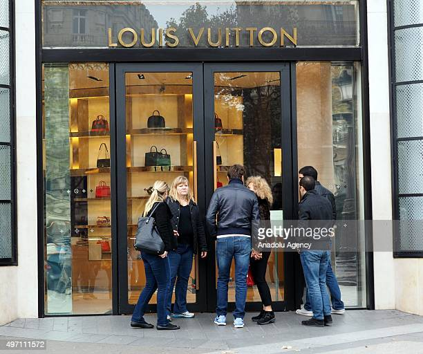 People stand in front of the Louis Vuitton store which is temporarily closed at the Champs Elysee in Paris France on November 14 2015 following the...