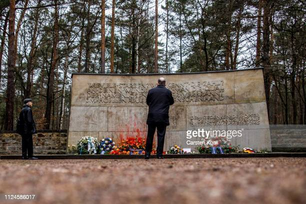 People stand in front of the memorial at the Heidefriedhof cemetery to commemorate the 74th anniversary of the firebombing of the city during World...