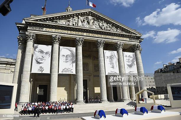 People stand in front of the Pantheon where drawings representing French politician Jean Zay French resistant Genevieve de GaulleAnthonioz French...
