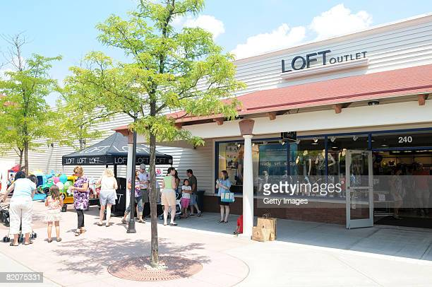 People stand in front of the store during an Ann Taylor LOFT grand opening at the Chelsea Wrentham Outlet July 26 2008 in Wrentham Massachusetts
