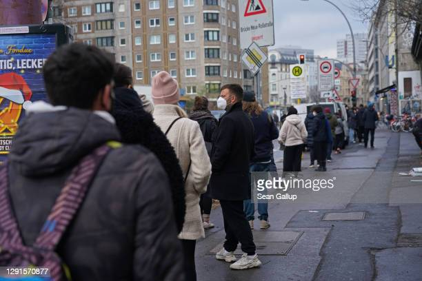 People stand in line around the block as they wait to take a rapid antigen Covid test at the KitKat Club on the first day of a nationwide hard...