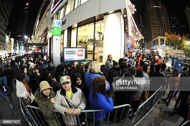 People stand in line as it wraps around the block outside of Macy's department store late November 24 2011 in New York as they wait for the midnight...