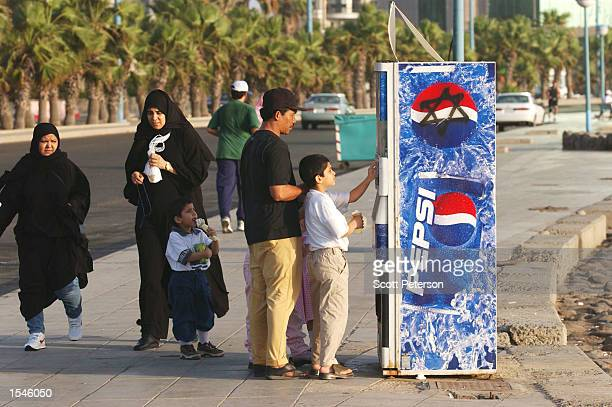People stand in line at a Pepsi Cola vending machine May 20 2002 in Jeddah Saudi Arabia A Star of David is spraypainted on the side as reminder to...