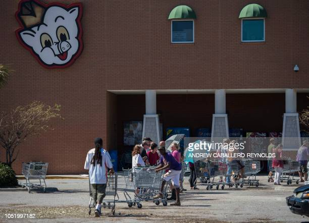 People stand in line at a supermarket in Port Saint Joe Florida on October 12 two days after hurricane Michael hit the area Rescue teams using...