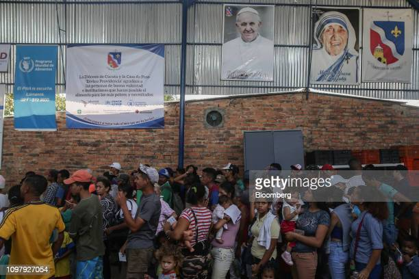 People stand in line at the Casa de Paso La Divina Providencia soup kitchen during a meal service for Venezuelan migrants in the town of La Parada...