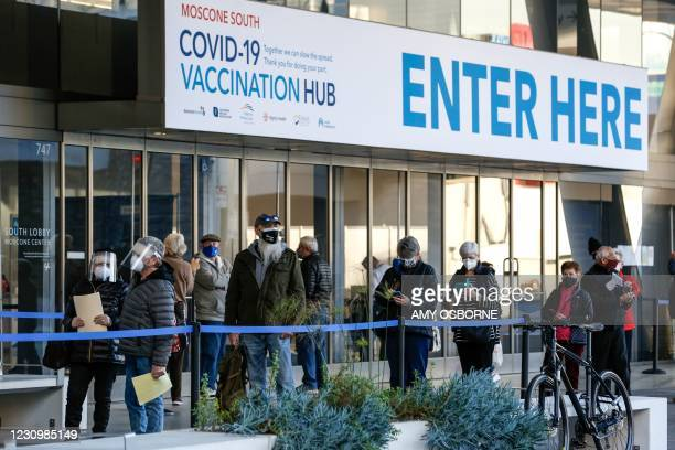 People stand in line at the mass vaccination site at San Francisco's Moscone Convention Center that opened today for healthcare workers and people...