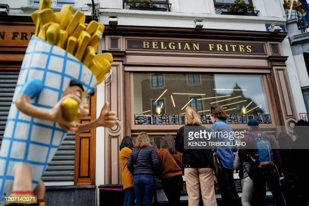 People stand in line in front of a French fries vendor near the Grand Place in central Brussels, on March 14 amid the outbreak of COVID-19, caused by...