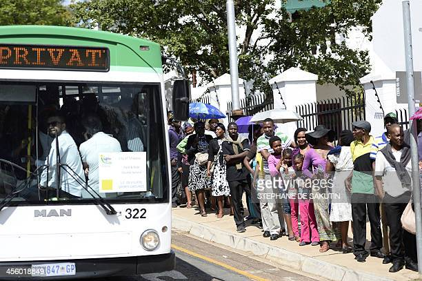 People stand in line next to buses on their way to see South African former president Nelson Mandela on the last day of Mandela's lying in state at...