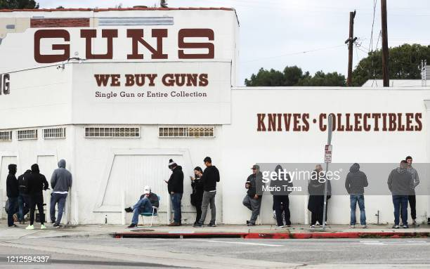 People stand in line outside the Martin B Retting Inc guns store on March 15 2020 in Culver City California The spread of Coronavirus has prompted...