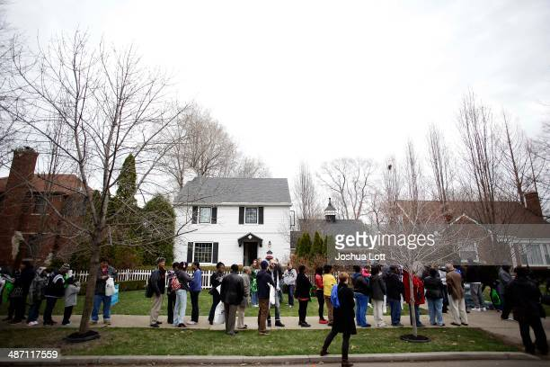 People stand in line to board a bus before touring one of twelve homes being auctioned off in the East English Village neighborhood April 27 2014 in...