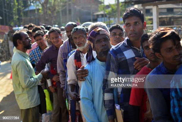 People stand in line to check their names on the first draft of the National Register of Citizens at Gumi village of Kamrup district in the Indian...