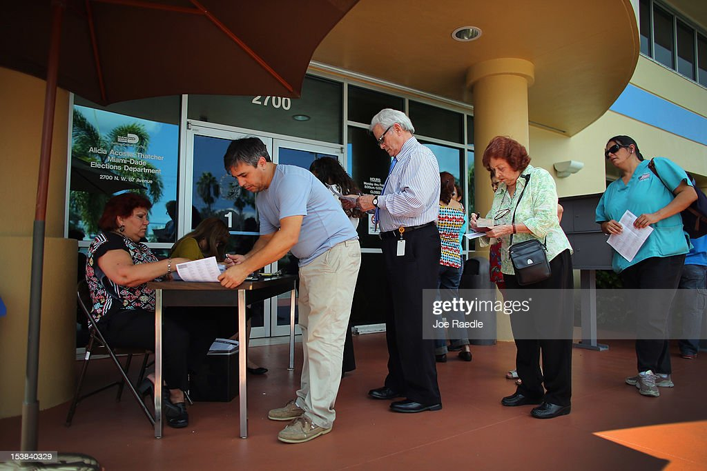 People stand in line to deliver their voter registration forms to a Miami-Dade Elections Department officials on the final day for voters to register to vote in the upcoming elections on October 9, 2012 in Miami, Florida. The Republicans and Democrats are battling it out for the election, less than a month away.
