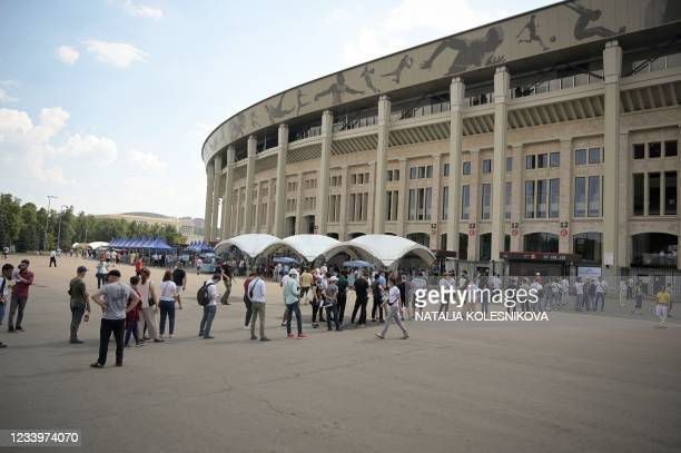 People stand in line to get a dose of Russia's Sputnik Lite Covid-19 vaccine at a vaccination point for foreigners at the Luzhniki stadium in Moscow...
