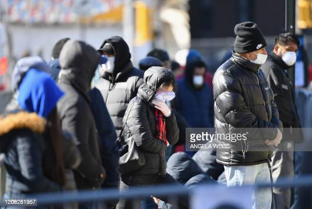 People stand in line to get tested for the coronavirus at Elmhurst Hospital Center in the Queens borough of New York City on March 26 2020 Elmhurst...