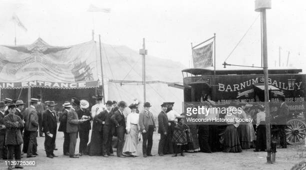People stand in line to purchase tickets at a Barnum & Bailey Circus ticket wagon near the main tent, 1903.