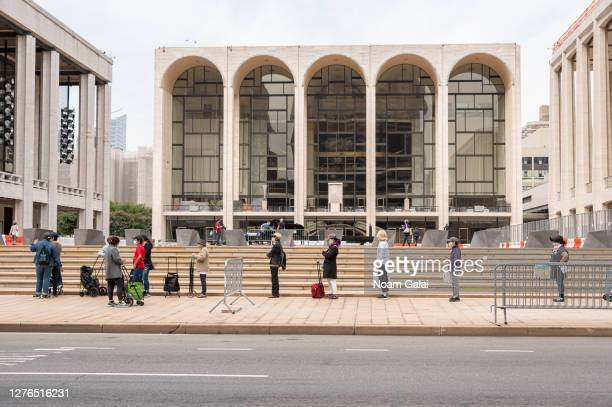 People stand in line to receive food donations at a Food Bank for New York City pop up food pantry outside Metropolitan Opera House at Lincoln Center...