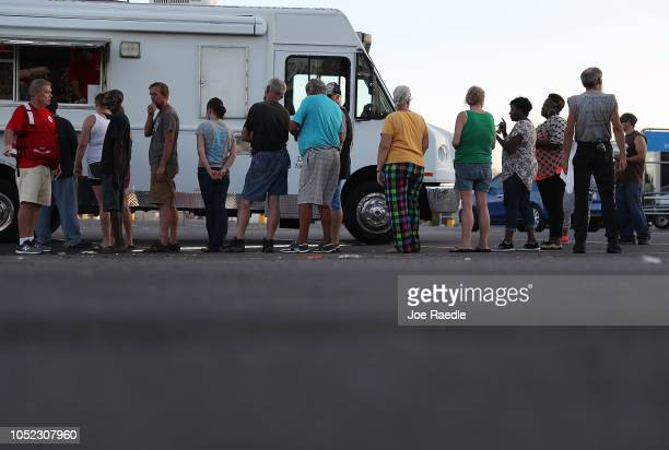 People stand in line to receive food from the Salvation Army emergency disaster services food distribution operation for people trying to recover...