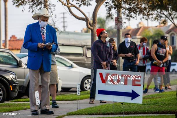 People stand in line to vote as the sun rises at the Main Street Branch Library vote center on November 3, 2020 in Huntington Beach, California....