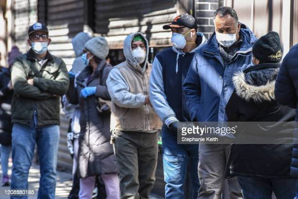 People stand in line while wearing face masks in the Elmhurst neighborhood on April 1 2020 in New York City With more than 75000 confirmed cases of...