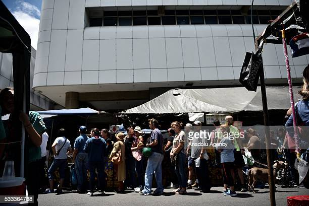 People stand in lines to buy eggs at a local supermarket in Caracas Venezuela on May 21 2016 Venezuelans minimum wage is 1505115 Bs according to the...