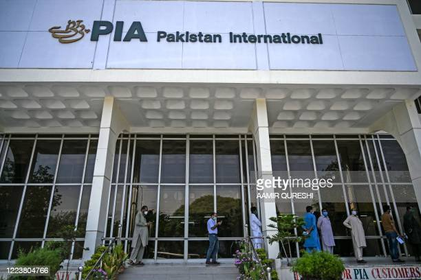 People stand in queue as they wait their turn to buy flight tickets outside Pakistan International Airlines office in Islamabad on July 1 2020...