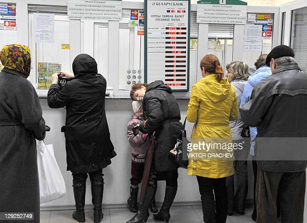 People stand in queue near a board listing foreign currency rates against the Belarus ruble inside an exchange office in Minsk on October 14 2011...