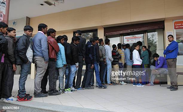 People stand in queue outside the ICICI Bank ATM machine to withdraw cash in sector14 on December 29 2016 in Gurgaon India