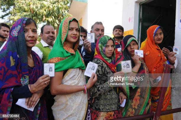 People stand in queue to cast their vote at a polling booth on February 11 2017 in Noida India Uttar Pradesh registered a voter turnout of 63% in the...
