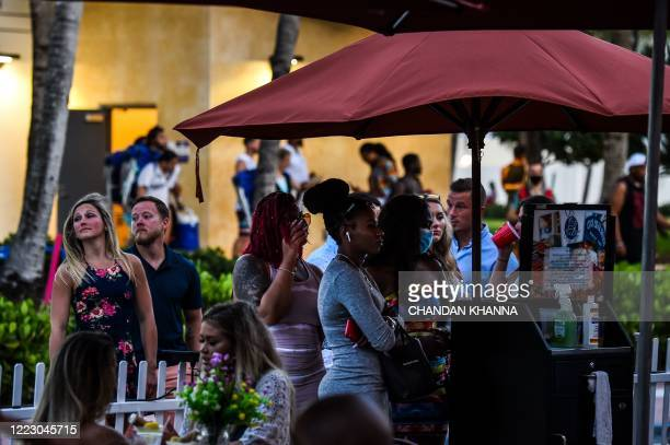 People stand in queue to enter a restaurant on Ocean Drive in Miami Beach, Florida on June 26, 2020. - They are itching for a good time after months...