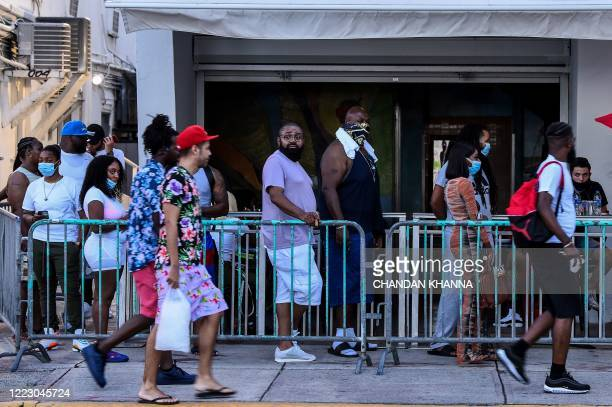 People stand in queue to enter a restaurant on Ocean Drive in Miami Beach Florida on June 26 2020 They are itching for a good time after months of...