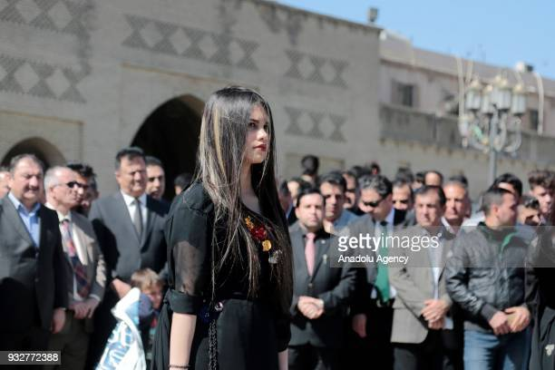 People stand in silence to commemorate the victims of Halabja massacre during a commemoration ceremony that organized due to 30th anniversary of...