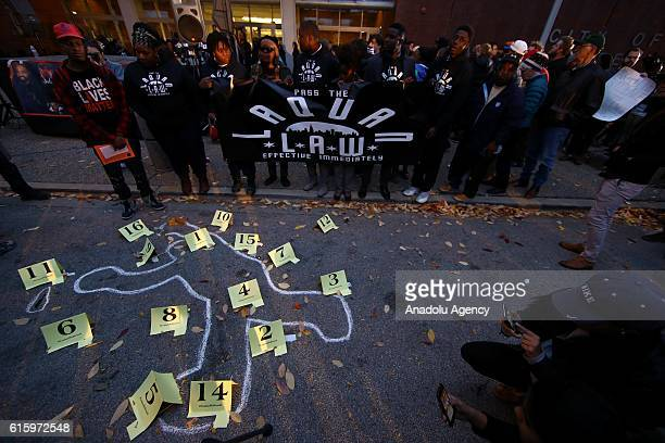 People stand in silent homage in front of the chalk outline drawn by supporters where Laquan McDonald shot and killed by police officers 2 years ago...