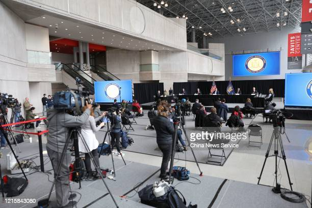 People stand in social distancing while attend a press conference of New York Governor Andrew Cuomo at Jacob Javits Convention Centre amid the...