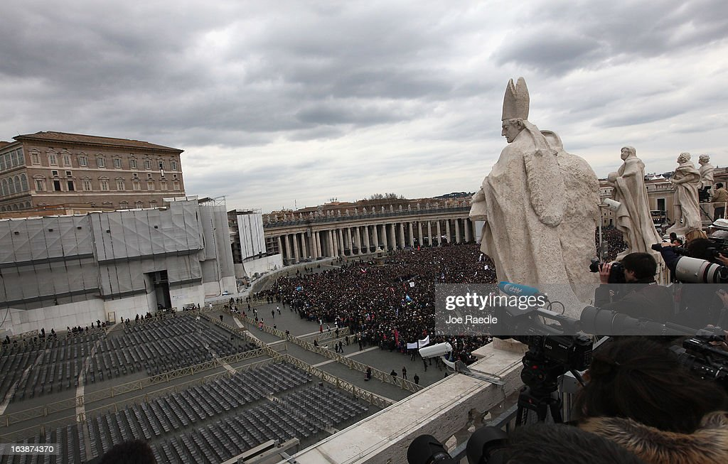 People stand in St. Peter's square as Pope Francis appears in the window of his apartment to recite the Angelus prayer on March 17, 2013 in Vatican City, Vatican. The Vatican is preparing for the inauguration mass of Pope Francis, the first ever Latin American Pontiff on March 19.