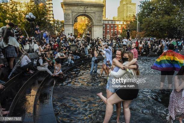 People stand in the fountain as they celebrate in Washington Square Park after it was announced that Democratic nominee Joe Biden would be the next...