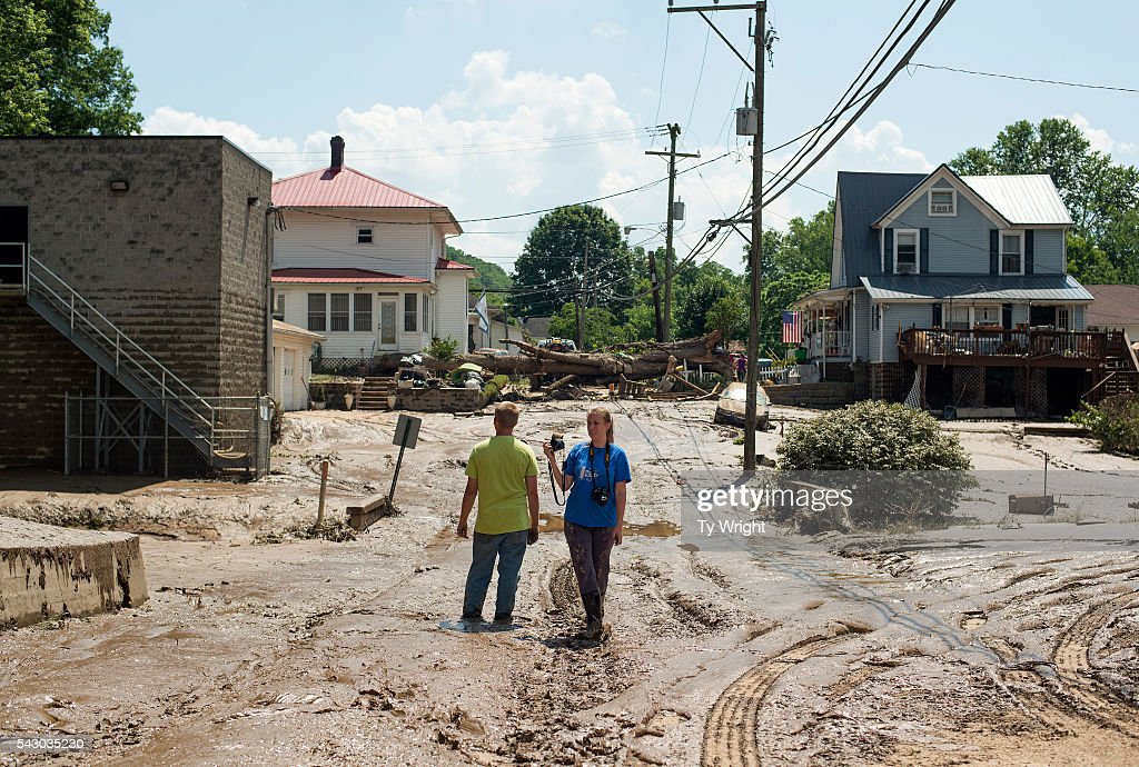 People Stand In The Middle Of A Mud Covered Street Left Over From The News Photo Getty Images