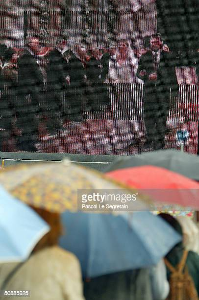 People stand in the rain as they watch the wedding between Spanish Crown Prince Felipe de Bourbon and former journalist Letizia Ortiz at the Almudena...